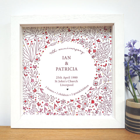 40th anniversary gift with flowery design, gold accents and personalised with couples names, wedding date, place of wedding, city of wedding and details of their life together. Ruby red in colour. Framed in a white box frame