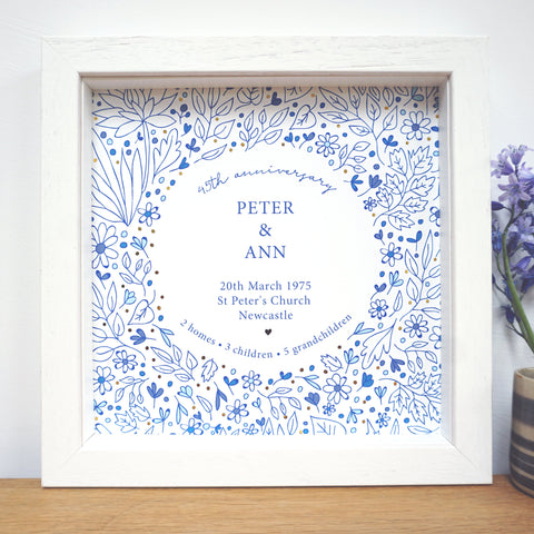 45th anniversary gift with flowery design, gold accents and personalised with couples names, wedding date, place of wedding, city of wedding and details of their life together. Sapphire blue in colour. Framed in a white box frame