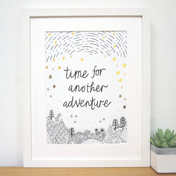 antdesigngifts.co.uk Monochrome and gold art print with the quote 'time for another adventure' with a hand drawn illustration of mountains, trees, sky and stars in white frame