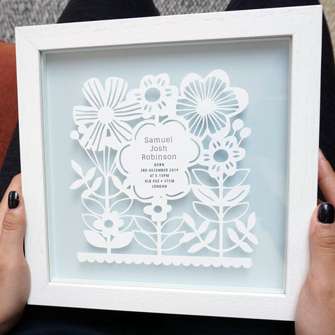 New baby boy gift papercut with gold foil. Blue background. Framed in a white floating frame. Personalised with baby statistics