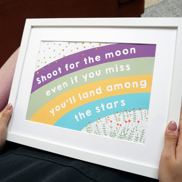 Shoot for the moon land among the stars rainbow print with gold foil stars and a field of flowers
