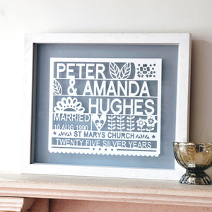 antdesigngifts.co.uk 25th anniversary gift papercut personalised with names, wedding date, venue and twenty five silver years. The design is cut out of card and framed in a floating frame