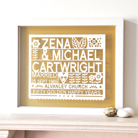 antdesigngifts.co.uk 50th anniversary gift papercut personalised with names, wedding date, venue and fifty golden happy years. The design is cut out of card and framed in a floating frame