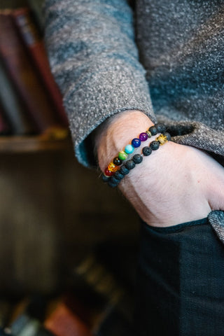 Man with hand in pocket, wearing healing chakra bracelets