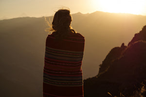 Peaceful shot of woman up the Andes Mountains reflecting and finding greater inner balance and well-being