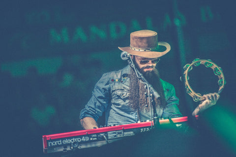 todd ogren playing tambourine and keyboard on stage with his django hat