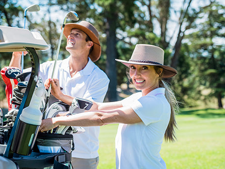 golfing couple wearing their soaker hat and breeze hat