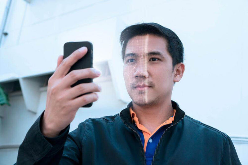 Man holding smartphone scanning face