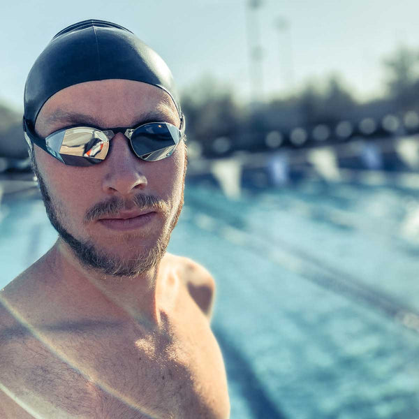 Man in swim cap takes selfie with pool in background while wearing Black Magic Mirror Silver goggles