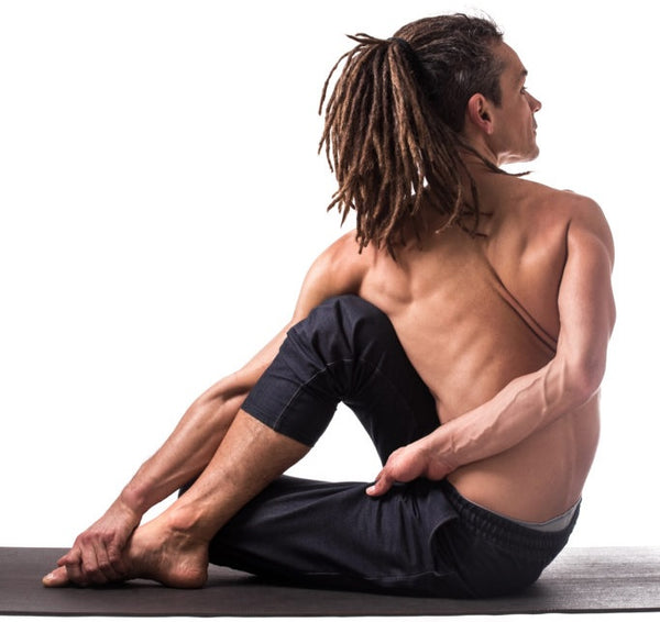 Homme pratiquant l'ashtanga yoga en posture de torsion