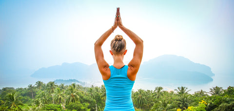 Woman in yoga pose overlooking tropical lanscape