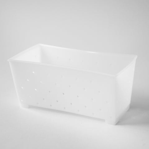 A small, white feta cheese mold sitting on a white surface.