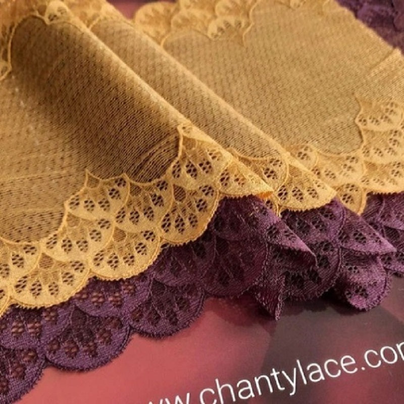 Ochre and Bordeaux colored lace ribbons laying on the ground showing their scallop edges