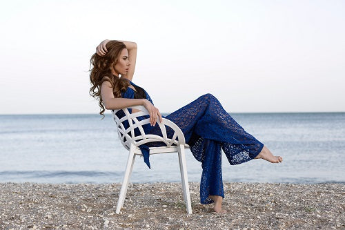 Woman in blue lace sitting at the beach