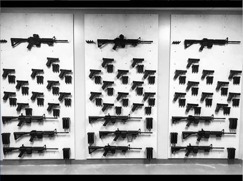 Picture of Spartan Mounts firearm mounts and firearm accessory mounts on a wall, including rifle mounts, handgun mounts, and magazine mounts