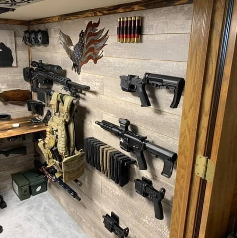 Picture of a gun wall with Spartan Mounts on it, featuring rifle mounts, handgun mounts, and magazine mounts. Firearms are mounted with them
