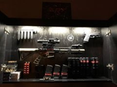 Picture of a gun box featuring a couple Spartan Mounts products, including a Spartan Mounts rifle mount, Spartan Mount handgun mounts, and Spartan Mounts magazine mounts. Also has a Spartan Mounts sticker on it