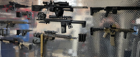 Gun wall that features many Spartan Mounts, including Spartan Mounts rifle mounts, Spartan Mounts handgun mounts, and Spartan Mounts magazine mounts