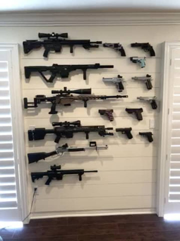 A single gun wall with a collection of handguns, rifles, and magazines all held up by Spartan Mounts, including rifle mounts, handgun mounts, and magazine mounts