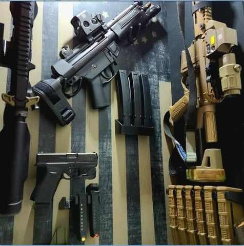Picture of gun wall with Spartan Mounts products and firearms on it. Includes rifle mounts, handgun mounts, and magazine mounts from Spartan Mounts to hold up rifles, handguns, and magazines