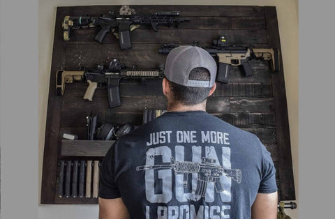 Picture of a man looking at his gun wall featuring rifle mounts and magazine mounts from Spartan Mounts' collection of firearm mounts