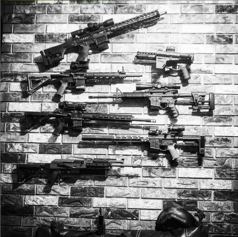 Picture of different rifle mounts mounted on a brick wall. All mounts are from Spartan Mounts and one rifle is tilted up