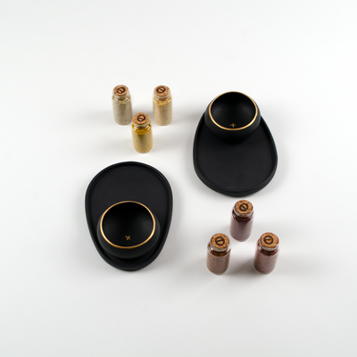 Mezcal gift set featuring two black and gold porcelain paring plates with copitas and six tasting salts