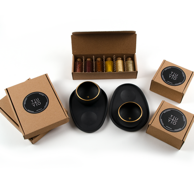 Packaging for mezcal gift set featuring two black and gold porcelain paring plates with copitas and six tasting salts