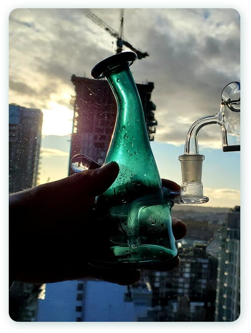Hand holding up a dabbing rig outside in Vancouver