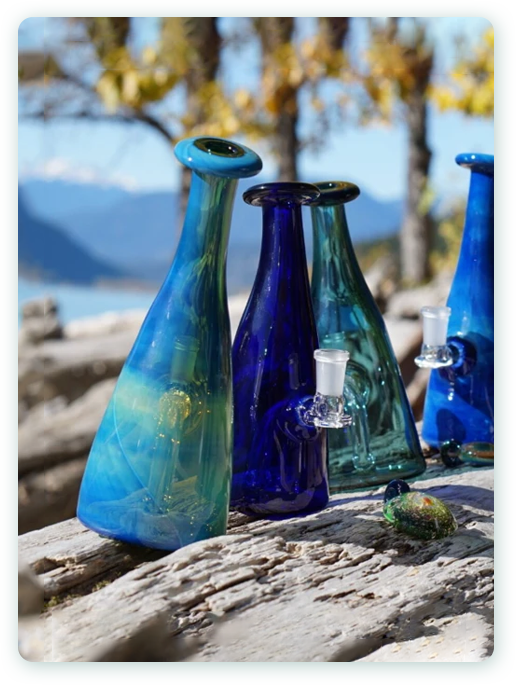 The Smoking Quartz bottle dab rigs sitting on a log, by the beautiful Lillooet lake and mountain range