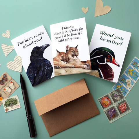 Three greeting cards with animal puns sitting on a light blue background surrounded by envelopes, stamps, pens and paper hearts.
