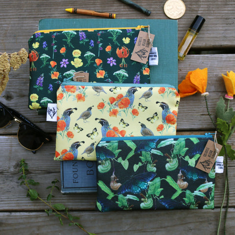 Zipper pouches with wildlife and plant watercolor prints and small items surrounding them