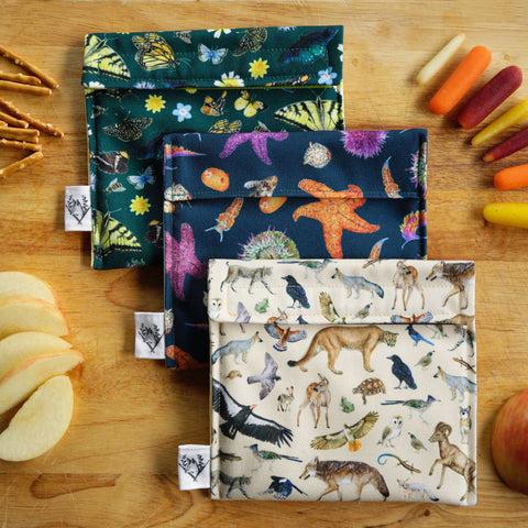 Three colorful reusable snack bags with watercolor animal and insect prints sitting on a wood chopping board surrounded by snacks like carrots, apples and pretzels.