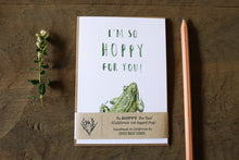 "One ""I'm So Hoppy For You!"" greeting card sits on a brown wood background, packaged with a paper loop describing the card."