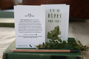 "Two ""I'm So Hoppy For You"" greeting cards sit side by side, standing up on top of a vintage natural history book, showing the front and back sides of the card."