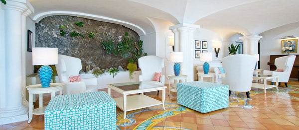 Photo of the lobby at the Hotel Marincanto in Positano, Italy. There is a piece of exposed cliffside on which the hotel is perched in the middle of the photo with a living wall of sorts consisting of plants growing out of the cliffside. White, mid century modern style chairs decorated with pink pillows and surrounded by geometrically patterned tables. Lambs with baby blue vases and framed photos add to the scene. A classic Italian tiled floor with matching light blue and yellow accents makes up the base of the photo.