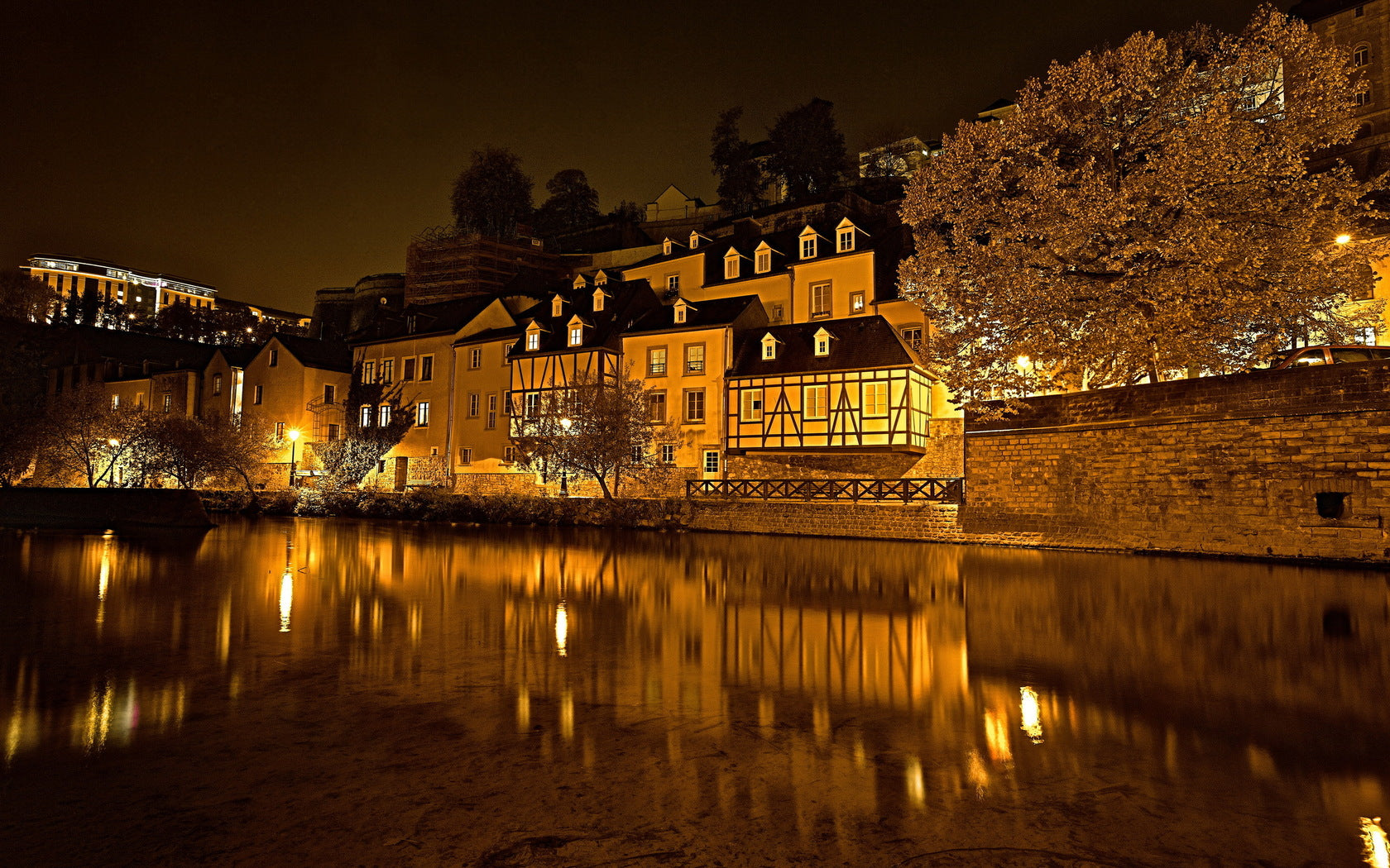 Luxembourg at night, at river level. A beautiful cabin style buildings sits on the river with the rest of the city slightly visible in the distance.