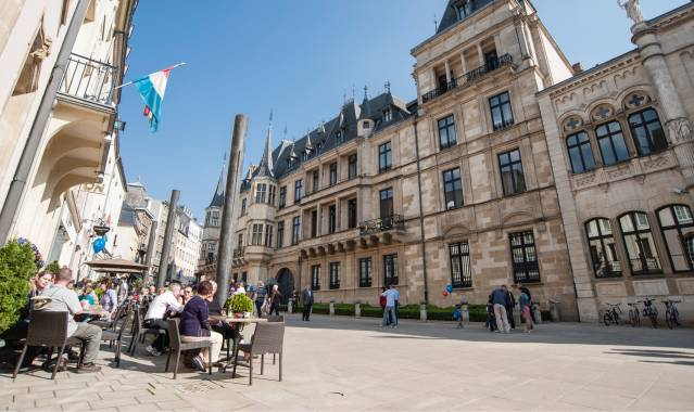 Photo of the central town square in the city of Luxembourg. Photo is taken from low to the ground on the left hand side and panning up and to the right. It shows a cafe or restaurant on the left with tables, chairs and patrons enjoying the sunny weather and food and drinks outside in typical European fashion. The street is made of interlocking cobblestone . There is a balcony above the cafe or restaurant with the flag of Luxembourg attached. to the right, an old colonial style building that looks as if it may belong to the government or some sort of political offices. The buildings are met by a deep blue sky on this sunny day with not one cloud in the sky.