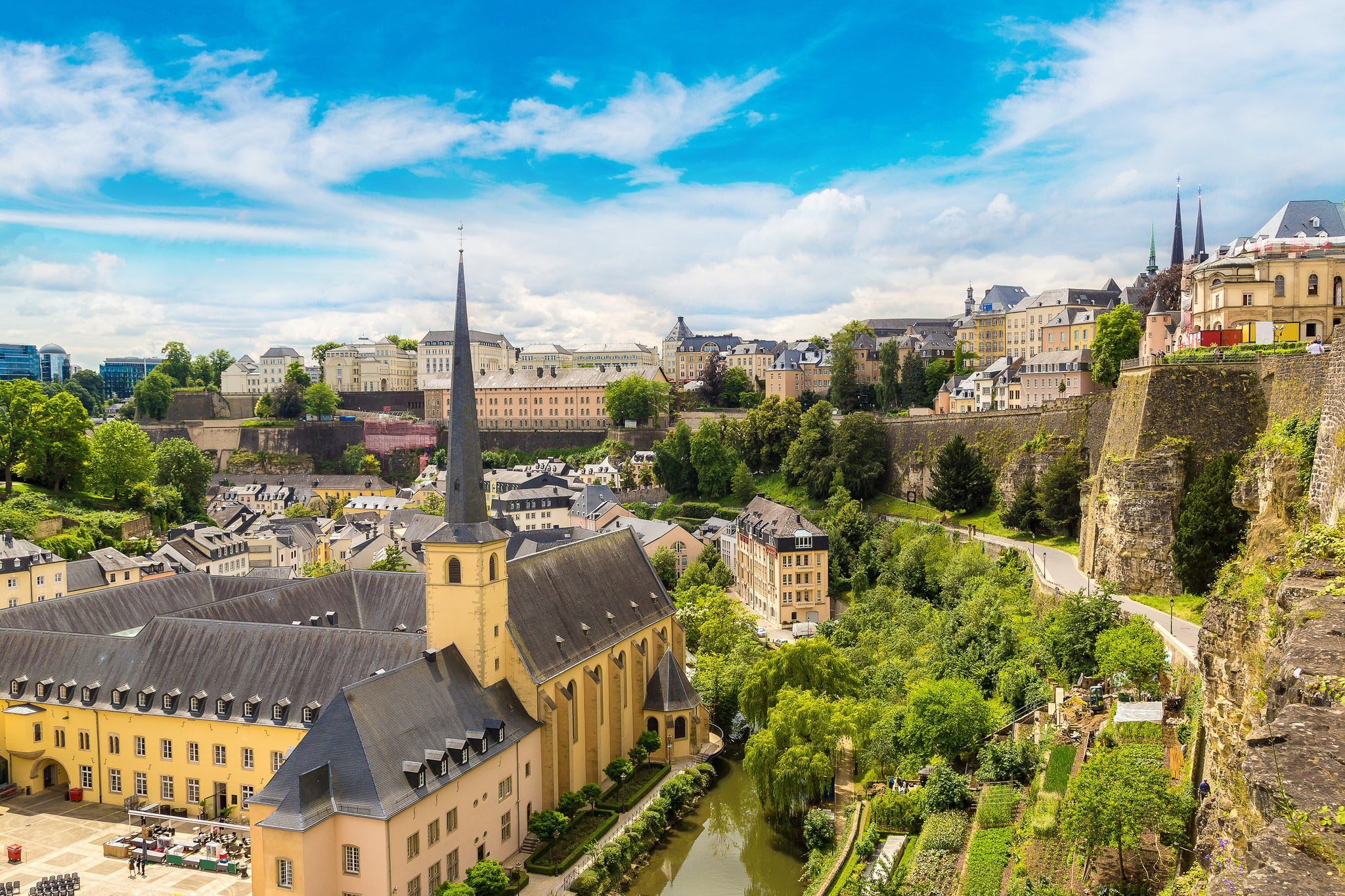 Photo of Luxembourg City, Luxembourg from overhead. A large, yellow building with two courtyards and a tower on its right side extending to a point resembling the tower of a church is situated closest to the viewer or photographer.  Various other buildings surround the large yellow building both behind and beside it. A large castle defensive wall separates the far right side of the page and extends into the city, away from the photographer. Beautiful, colorful European style renaissance buildings line the streets and are met with modern high rise office buildings in the far left corner of the image. The sky is light blue with wispy clouds. Large bushy trees line the wall along with bright green grass. The are trees and greenery dispersed throughout the city.
