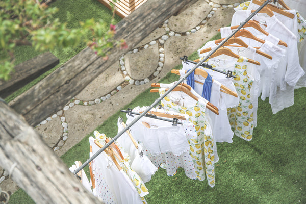 Photo taken overhead of an outdoor shop in Positano, Italy with all white, female garments line a clothesline hanging system featuring the signature lemon print that Positano is known for.