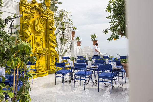 Photo of the sitting area at Franco's Bar in Positano, Italy. Blue chairs surround white tables and an accent piece to the left which has been painted from its original colour to Yellow. Shining white tile floors and the beautiful background oif the