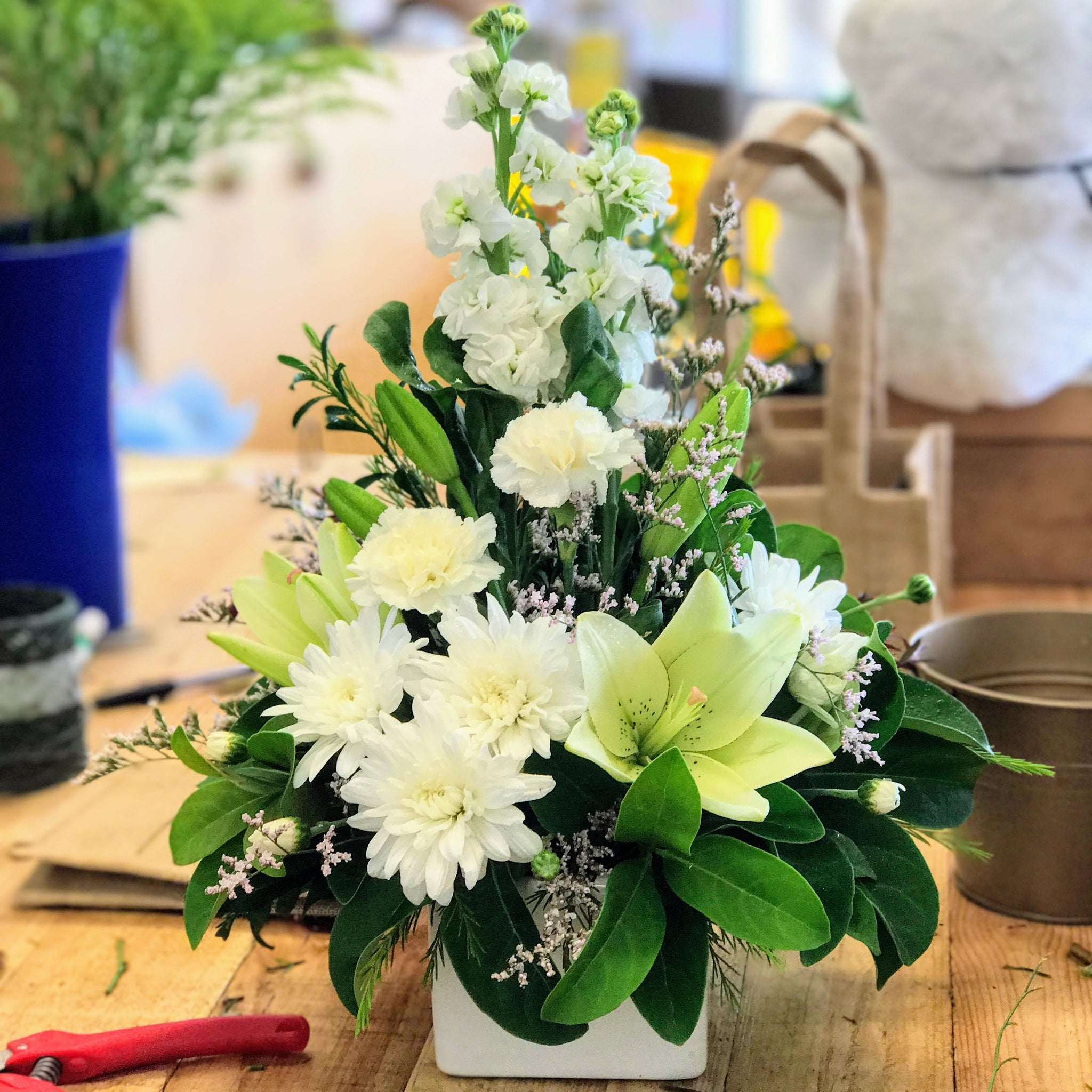 The La Bella flower arrangement combines a selection of soft whites and cream flowers to a traditional looking flower arrangement.   White stock, Lilium, chrysanthemum and carnation make up an upright elegant arrangement  in a classic white ceramic container.