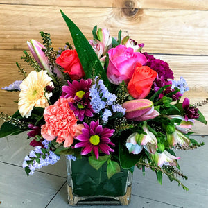 Frida is a colourful, compact arrangement of mixed blooms in shades of bright pinks, deep mauves, soft blues, lemon and a little pop of cream, expertly arranged by Enoggera Flowers in a glass cube vase.   Our Frida arrangement is available for delivery to most Brisbane suburbs, or for pick up at our store in Enoggera