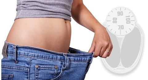 woman holding jeans near her stomach