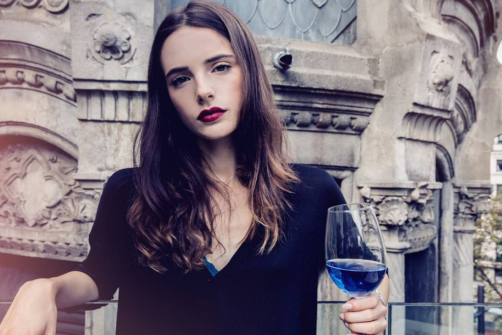 Woman drinking a glass of blue wine