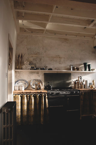 directional sunlight in rustic style kitchen with curtains and decorative antiques