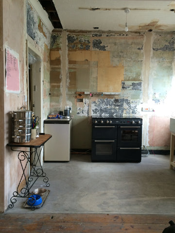 A kitchen half way through renovation with distressed walls and concrete floor