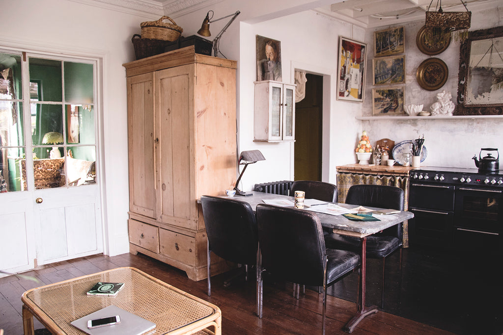 white walled rustic country kitchen interior with large antique pantry cupboard