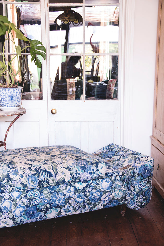 Blue and white flower fabric on upholstered antique ottoman