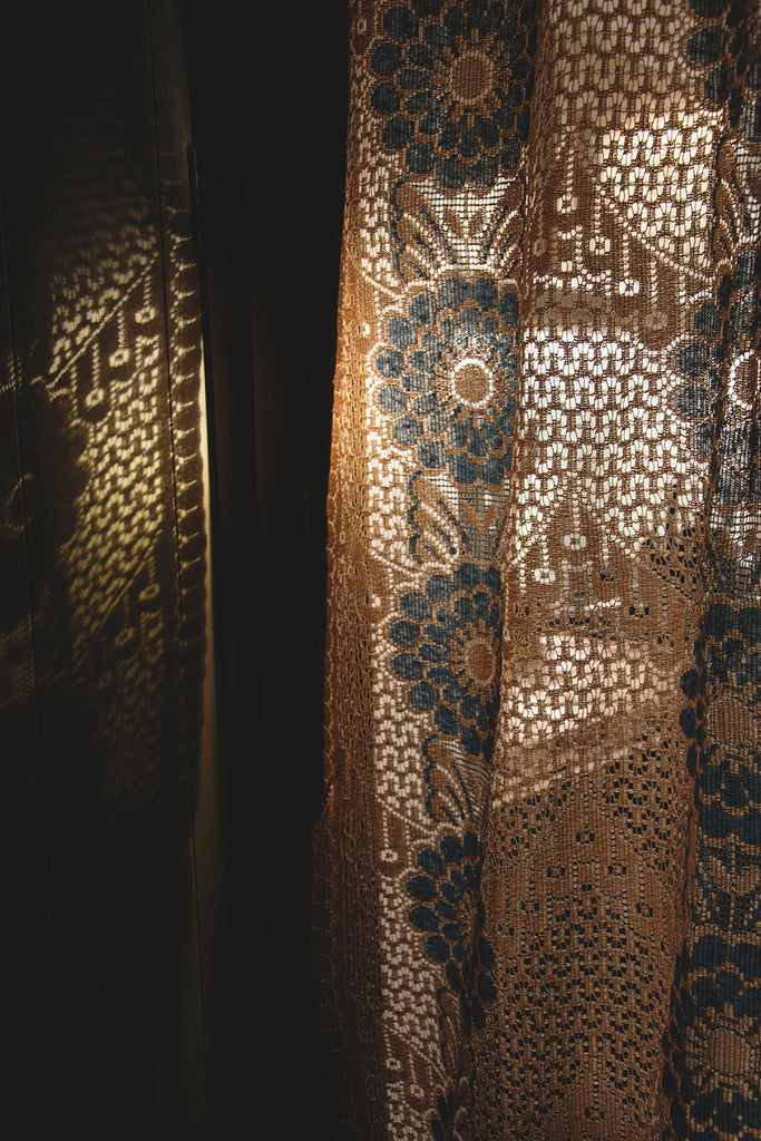 Antique lace curtain in blue and gold.